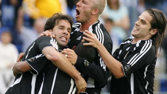 David Beckham (c), y Fernando Gago (d), felicitan a su compañero, el delantero holandés Ruud Van Nistelrooy (i), tras marcar de penalti el segundo gol (Efe).