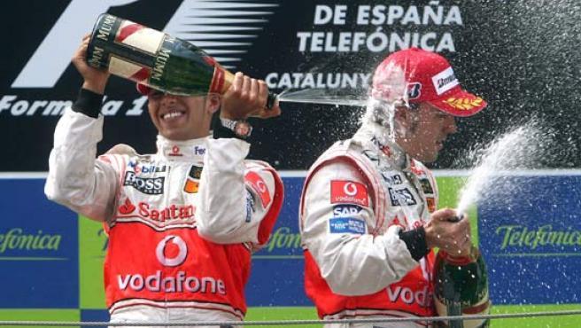 Los pilotos Lewis Hamilton y Fernando Alonso, antiguos compañeros en McLaren, celebran con champán su segundo y tercer lugar respectivamente en el pasado Gran Premio de España.