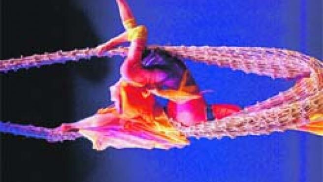 Sobre unos lazos una trapecista interpreta su número en las alturas.