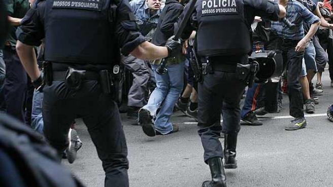 Dos mossos arrinconan a un grupo de manifetantes durante la protesta del sábado pasada en Barcelona. (EFE)