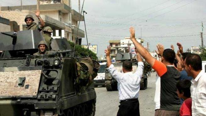 Un contingente de soldados del ejército libanés es saludado por ciudadanos a la entrada del campo de refugiados de Nahr el Bared. (Foto: EFE)