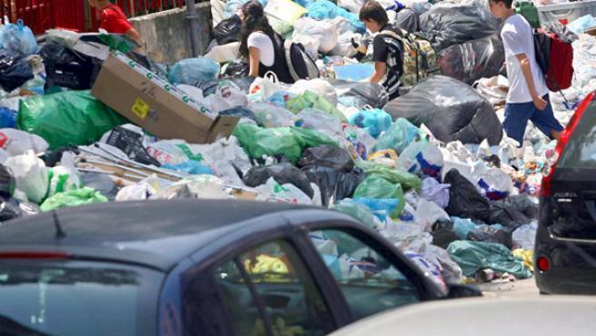 Un grupo de estudiantes atraviesan la basura acumulada en la ciudad de Nápoles (EFE/CIRO FUSCO)