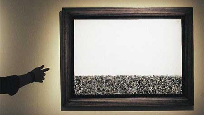 Una de la obras de la exposición y Rafael Canogar posando frente a una suya. Además de él, hay obras de Antonio Saura o Martín Chirino. (Biel Aliño / Efe).