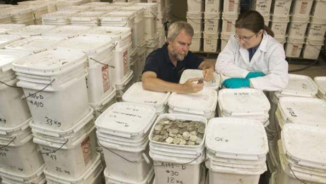 """Greg Stemm y una empleada de Odyssey Marine Exploration examinan parte del tesoro del """"Cisne Negro"""" (AP Photo/Odyssey Marine Exploration)"""