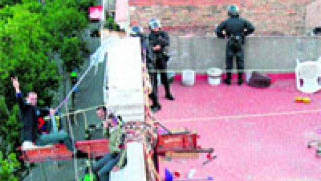 La casa Miles de Viviendas va ser desallotjada de matinada i alguns joves es van penjar a la façana abans dels disturbis al carrer (MDV / ACN / EFE).