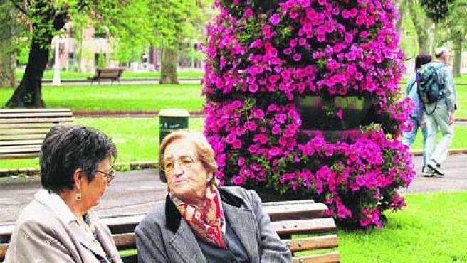 Dos mujeres conversan, ayer, junto a una jardinera que ha sufrido el expolio de varias de sus flores. (B. H.).