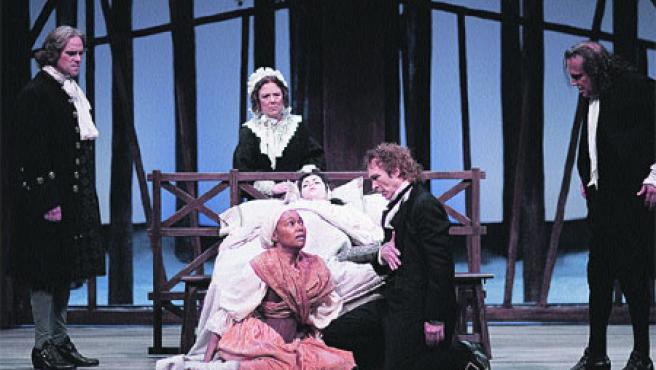 Al pie de la cama, el reverendo Hale (Juan Ribó) con Tituba (Lia Chapman), la esclava que origina la caza de brujas.