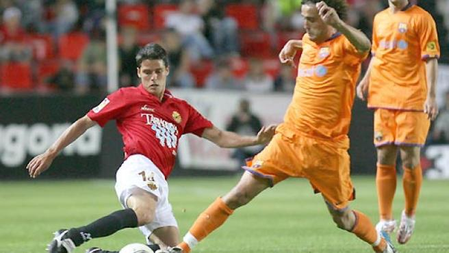 El jugador del Nastic, Oscar López (i), intenta cortar el avance del jugador del F. C. Barcelona, Ezquerro. (EFE).