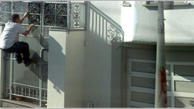 Un hombre saltando una verja, pillado por Google Street View.