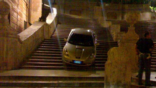 El coche baja, anclado en la escalera de la plaza de España de Roma.