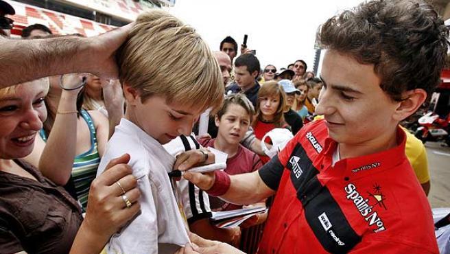 Jorge Lorenzo firma un autógrafo a un joven aficionado. (Efe)