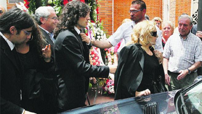 Raúl y Javier (con el pelo largo), dos de los hijos de El Fary, y su viuda (dcha.) junto al coche fúnebre. (Lerena / Efe)