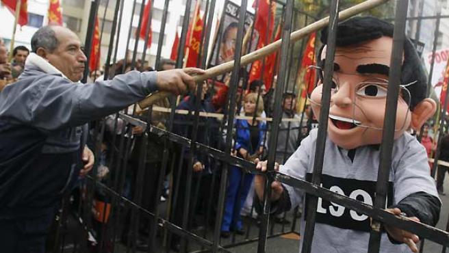 Un hombre golpea a un muñeco que representa a Fujimori en una manifestación de trabajadores despedidos durante su mandato, frente a la embajada de Chile en Lima. (REUTERS).