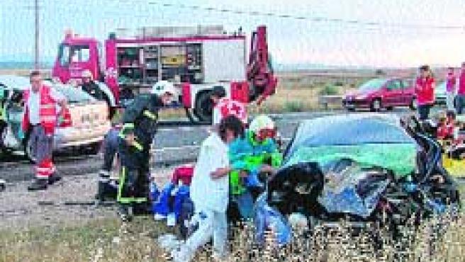 Bomberos y sanitarios, trabajando ayer en el coche accidentado en la M-509, en Madrid.