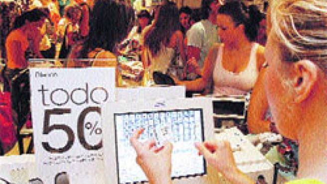 Una dependienta mira el precio de una prenda en una tienda llena ayer de gente.(José Rojas)