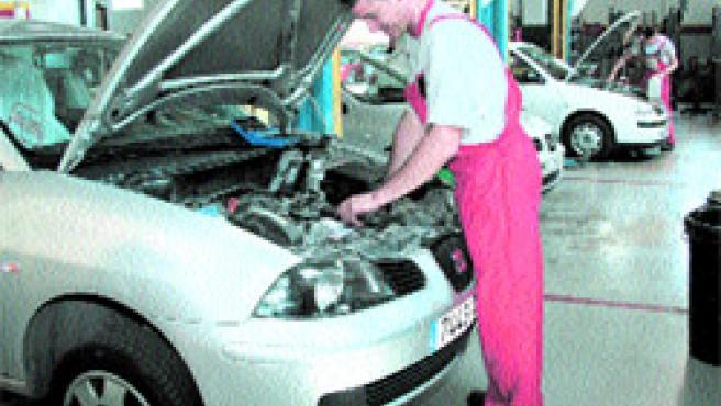 Dos mecánicos de Ginés Huertas se emplean a fondo para aliviar la lista de espera (Lara Roda).
