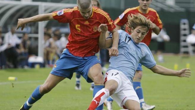 Juan Surraco (d), de la selección de fútbol de Uruguay, disputa el balón con Gerard Pique (i) de España (EFE).