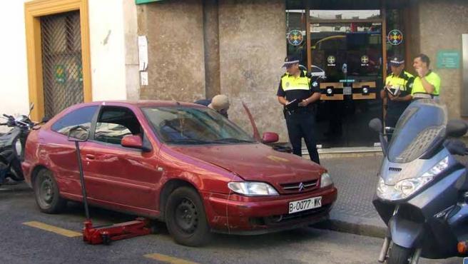Agentes de la Policía Local inspeccionan hoy un vehículo en el centro.
