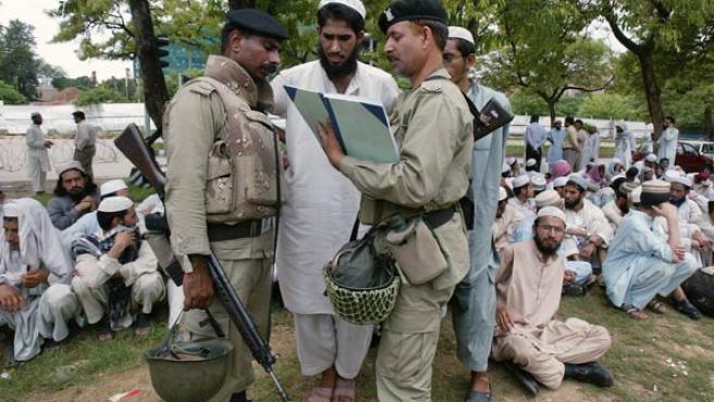 Miembros de las tropas paramilitares recaban los datos de un estudiante radical islamista después de su rendición (REUTERS)
