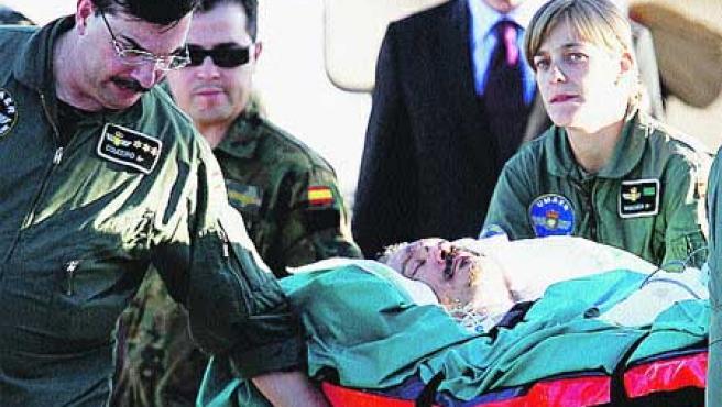 Uno de los heridos, en el momento de salir del avión en camilla. (Reuters).