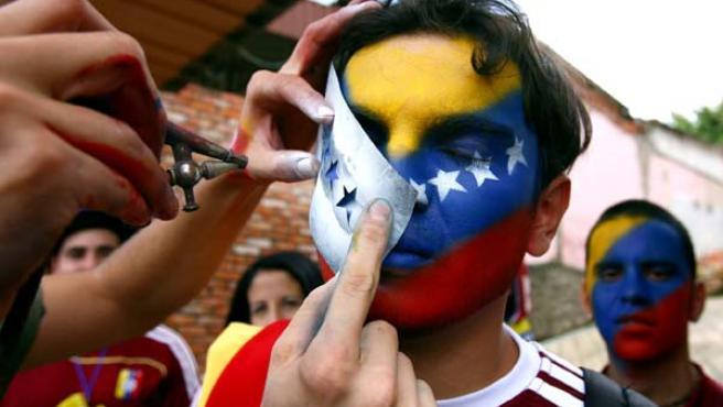 Seguidores de la selección de fútbol venezolana pintan sus caras con los colores de la bandera nacional (Efe).