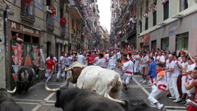 Los mozos corren delante de los toros a la altura de la curva de Mercaderes con la calle Estafeta.