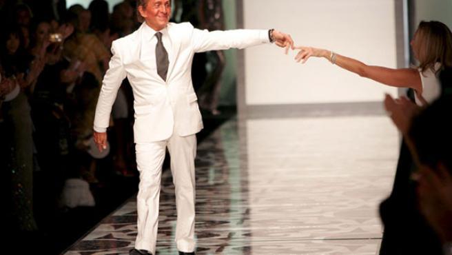 El diseñador Valentino saluda al final de su desfile de aniversario.