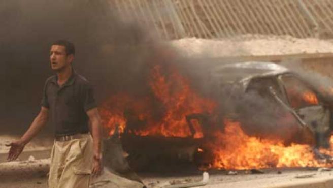 Un hombre pasa delante de uno de los coches incendiados por la explosión de un camión bomba en la ciudad de Kirkuk.