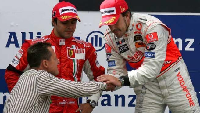 Alonso recibe la felicitación de Schumacher en presencia del brasileño Massa. (J. Buettner/EFE).