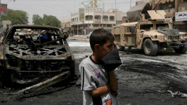 Un joven se cubre la boca un un pañuelo tras la explosón de un coche bomba en el barrio bagdadí de Karaba (MOHAMED JALIL/EFE)
