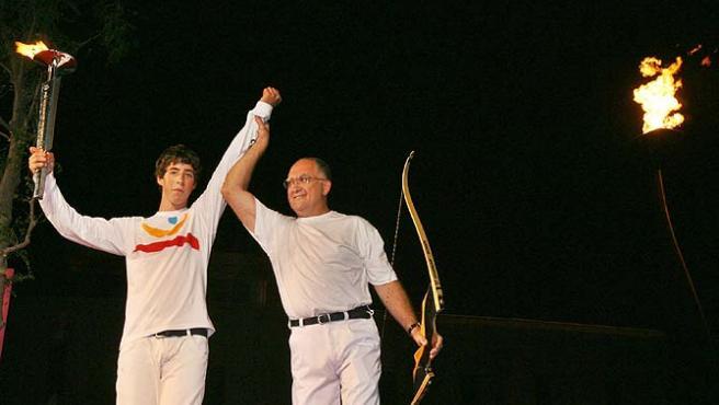 El pebetero del estadio Lluís Companys, ante el arquero Antonio Rebollo (d) y un joven deportista nacido en 1992. (Efe)