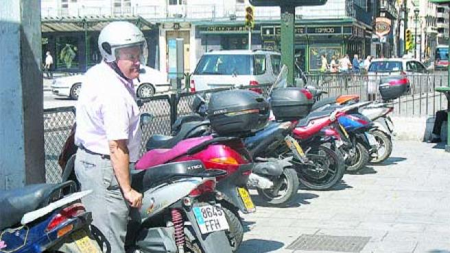 Un motorista, a punto de salir ayer con su moto del aparcamiento improvisado de la plaza de España.