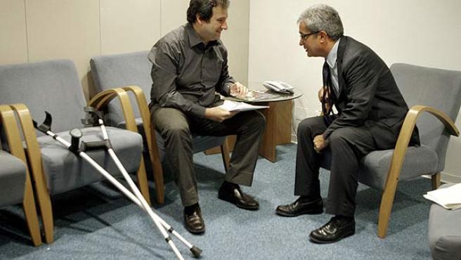 Jordi Hereu charla con el conseller de Interior, Joan Saura, junto a las muletas que utiliza estos días para caminar. (EFE)