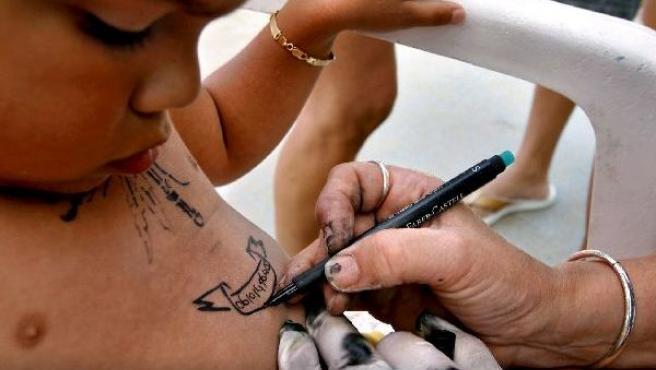 Una niña es tatuada en la playa de Sheveningen, Holanda.
