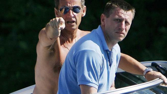 El presidente francés, Nicolas Sarkozy, señala a los fotógrafos, con gesto molesto, durante un paseo por el lago Winnipesaukee. (AP)