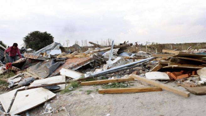 Un habitante de Las Barranquillas busca entre los escombros de una chabola.