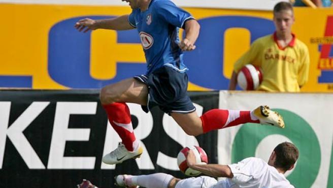 Giorgios Seitaridis (arriba), del Atlético, lucha por el balón con Laszlo Sepsi, del Gloria Bistrita. (Efe)
