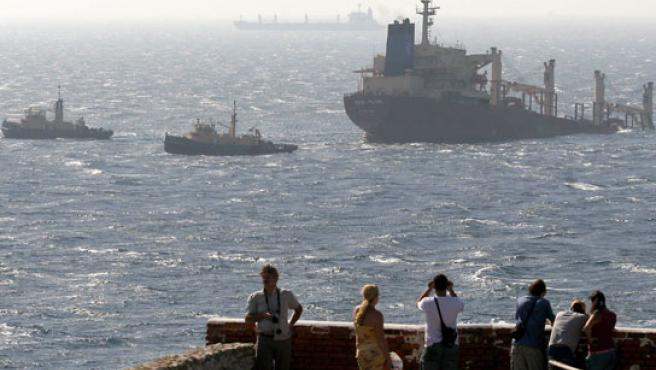 """Varios turistas observan el estado del buque chatarrero """"New Flame"""" que se encuentra semihundido."""