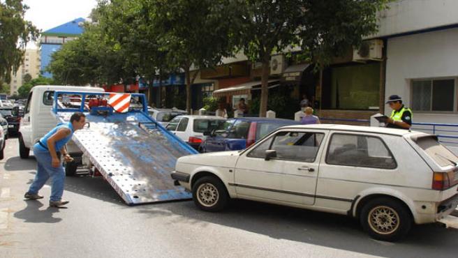 La grúa, foto de archivo, retira de la calle un vehículo presuntamente robado y abandonado.