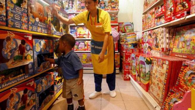 Una empleada de una juguetería en Manila atiende a un niño junto a varios juguetes de Fisher Price(efe/M.F.ALQUINTO).
