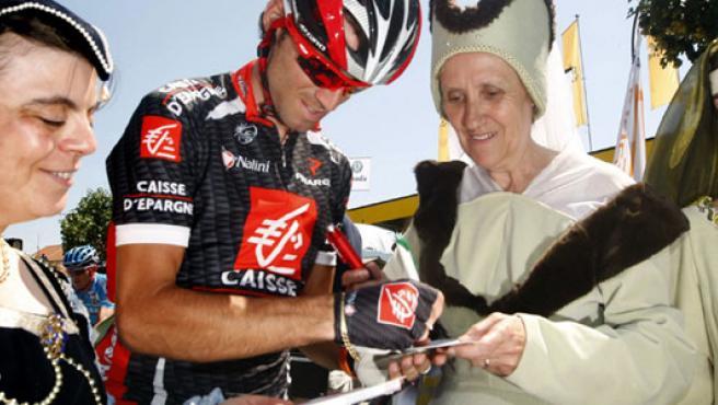El ciclista murciano Alejandro Valverde firma autógrafos a unas mujeres disfrazadas durante una etapa del Tour 2007 (EFE).