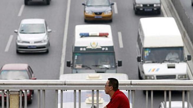 Un ciclista pedalea en un puente sobre un atasco en Pekín (China). (EFE)