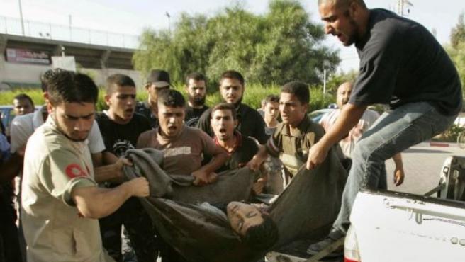 Un grupo de palestinos portan el cadáver de unos de los seis milicainos muertos en un bombardeo israelí (REUTERS).