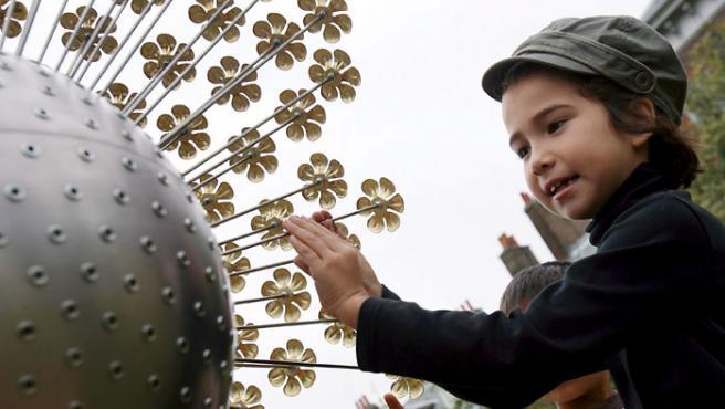 Una niña coloca una flor dorada en una instalación floral artística realizada en memoria de Diana de Gales en el Palacio de Kensington (Londres).