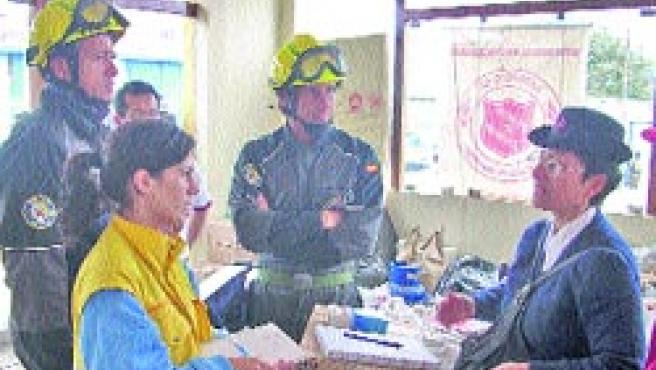 La médico andaluza y bomberos españoles, inspeccionando uno de los albergues de Pisco. (L. O)