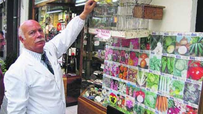 José Luis Blanco alimenta a los pájaros que tiene colgados a la entrada de su negocio, Droguería Alfonso.(U. E.)