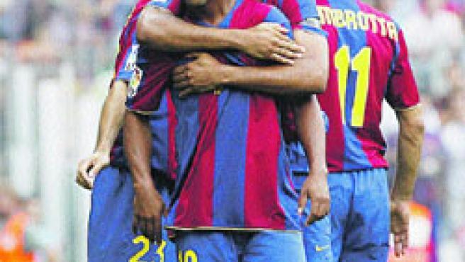 Henry y Ronaldinho se abrazan tras uno de los goles.(EFE)