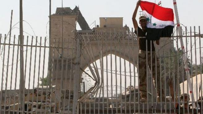 Un soldado iraquí enarbola la bandera de su país (Reuters)