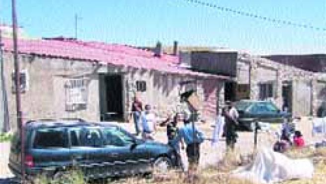 Varios de los vecinos rumanos, ayer, sentados a la puerta de algunas de las casas en las que conviven.