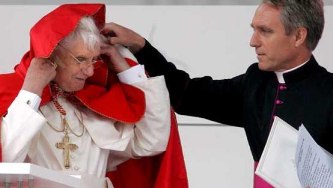 Benedicto XVI es asistido por su secretario, Georg Gaenswein (i), que le ayuda a arreglar su capa.